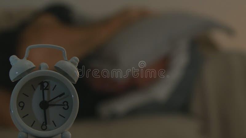 Imagem borrada com o homem cansado na tentativa má a dormir olhando para cronometrar a virada do alarme imagem de stock royalty free