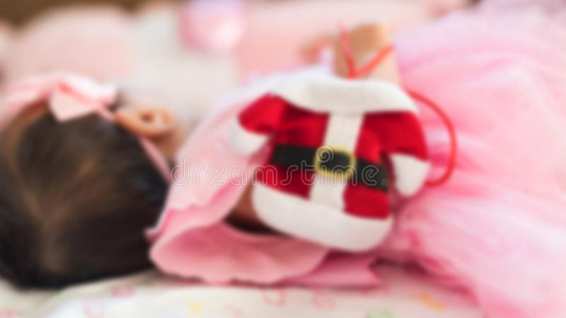 Imagem borrada da menina asiática recém-nascida adorável de Littte, 1 a 2 meses, com o vestido cor-de-rosa que guarda o terno ver fotografia de stock