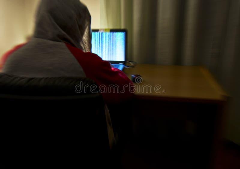 A imagem borrada de trás de um hacker com uma camiseta e uma capa aumentou apenas em sua sala usando um portátil para a segurança fotos de stock royalty free