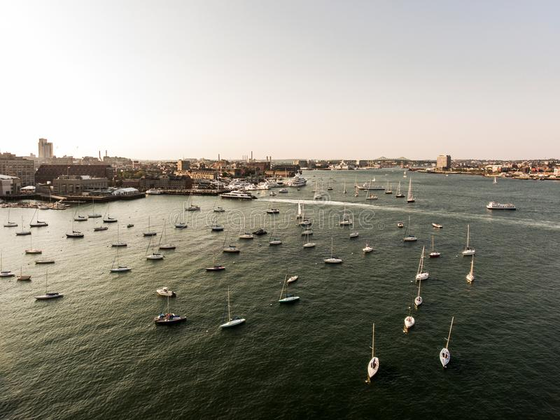 A imagem Boston miliampère da opinião aérea do voo do helicóptero, EUA durante o por do sol abriga com os barcos perto da baía da imagem de stock