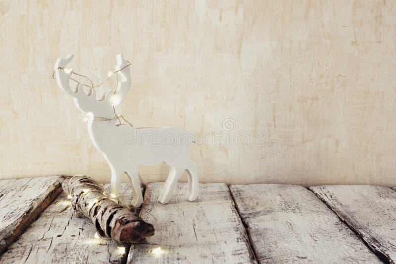 Imagem chave alta do log velho da árvore com luzes de Natal feericamente e do raindeer na tabela de madeira Foco seletivo Imagem  fotos de stock