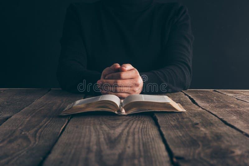 imagem colhida da freira que senta-se na tabela com a Bíblia imagens de stock royalty free