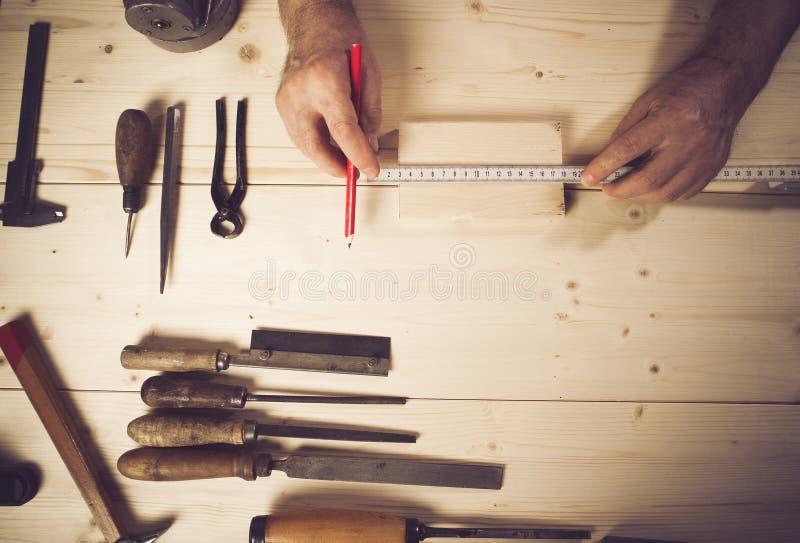 Imagem colhida da madeira de medição do carpinteiro superior na oficina fotografia de stock royalty free