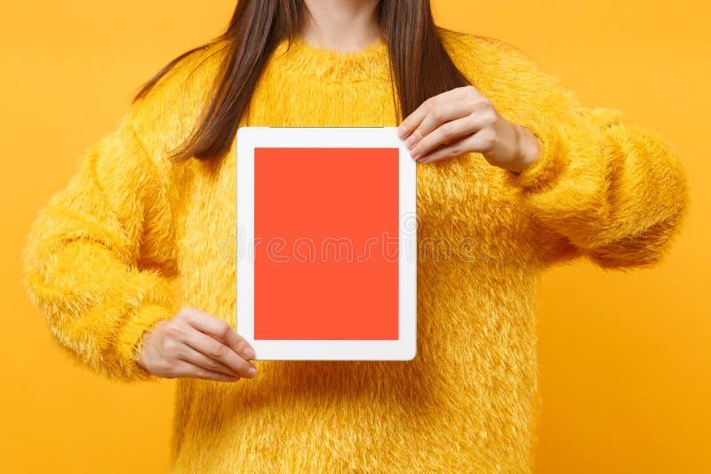 Imagem colhida da mulher moreno nova na camiseta da pele que mantém o computador do PC da tabuleta com a tela vazia preta vazia i foto de stock royalty free