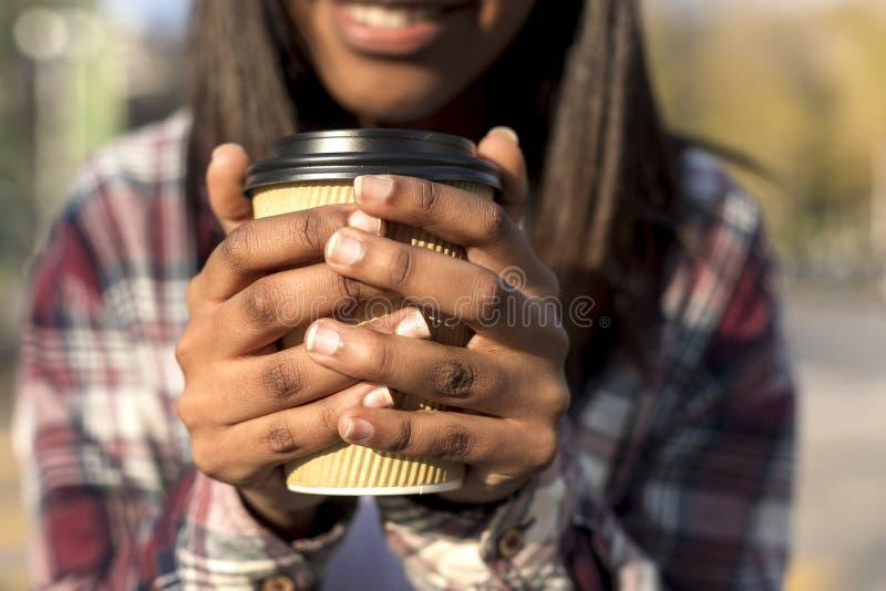 Imagem colhida da mulher negra nova de sorriso no copo da terra arrendada da camisa do moderno nas mãos foto de stock