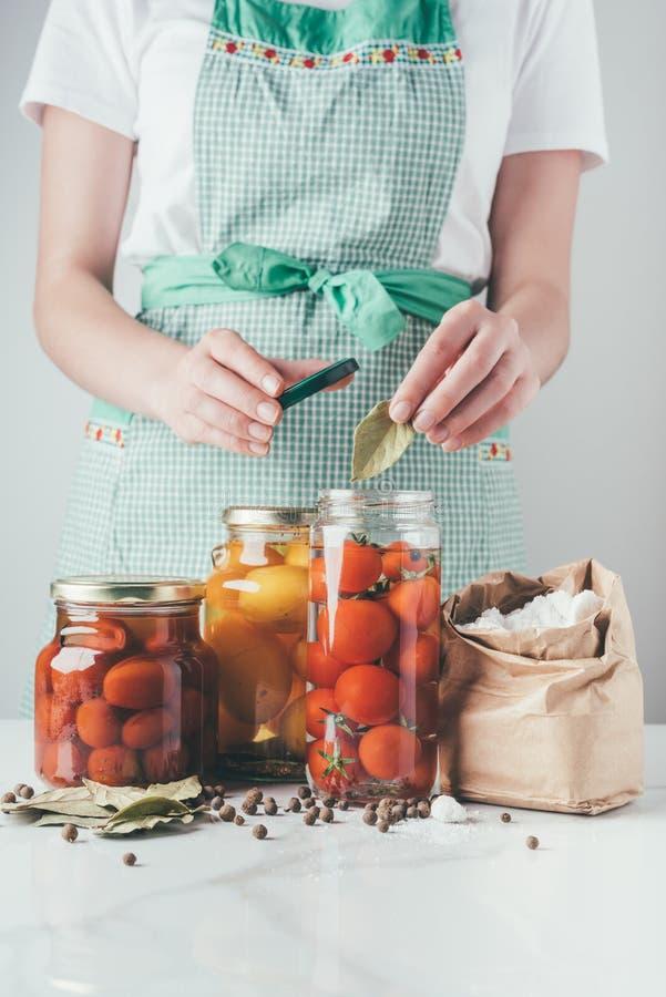 imagem colhida da mulher que adiciona a folha de louro a preservar tomates fotografia de stock royalty free