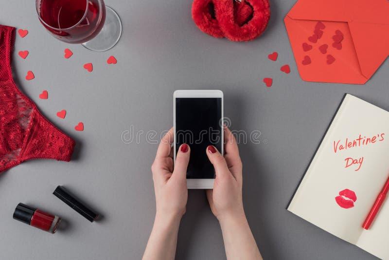imagem colhida da mulher que guarda o smartphone nas mãos, caderno com palavras imagens de stock
