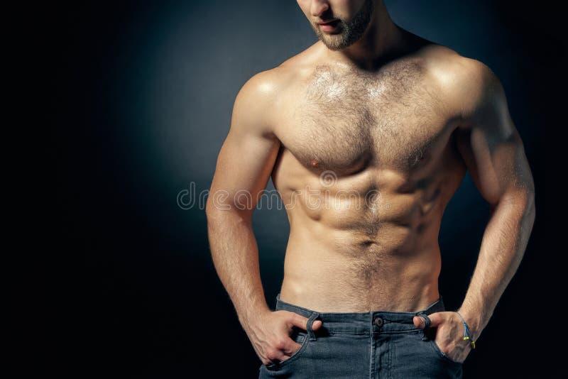 Imagem colhida de descamisado muscular com mãos em uns bolsos foto de stock