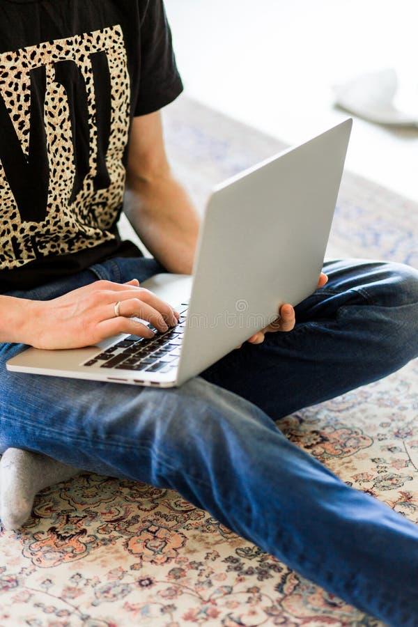 Imagem colhida de um homem novo que trabalha no computador que senta-se na tabela de madeira imagem de stock