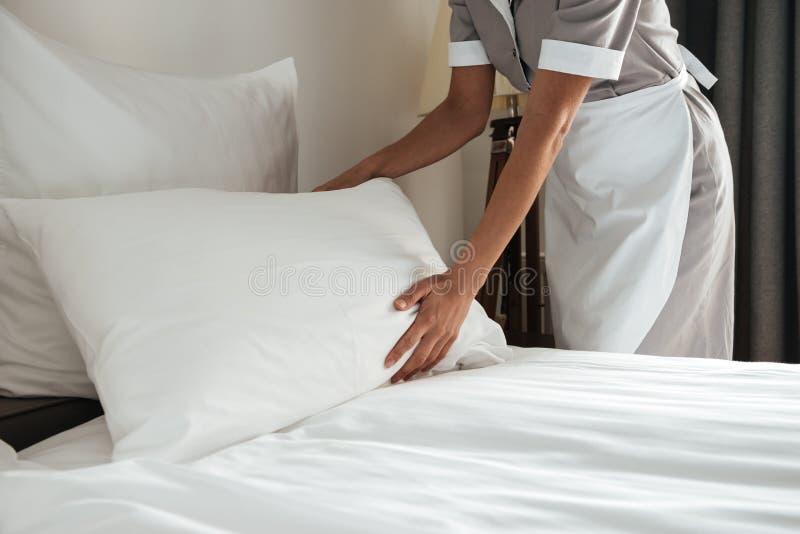 Imagem colhida de uma camareira que faz a cama na sala de hotel imagens de stock royalty free