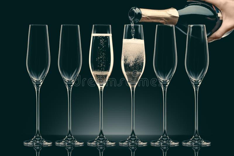 Imagem colhida do champanhe de derramamento da mulher da garrafa em seis vidros transparentes fotografia de stock