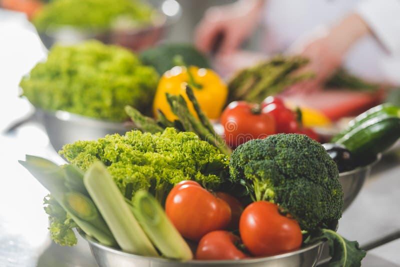 imagem colhida do cozinheiro chefe que cozinha na cozinha do restaurante com vegetais maduros foto de stock royalty free