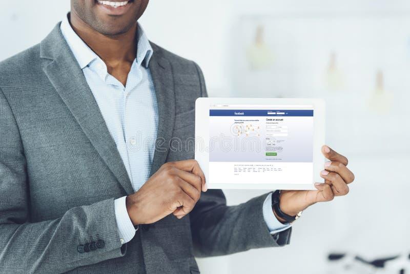 imagem colhida do homem afro-americano de sorriso que mostra a tabuleta com a página carregada do facebook imagem de stock royalty free