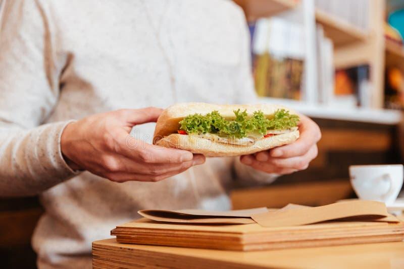 Imagem colhida do homem novo que guarda o sanduíche fotos de stock royalty free