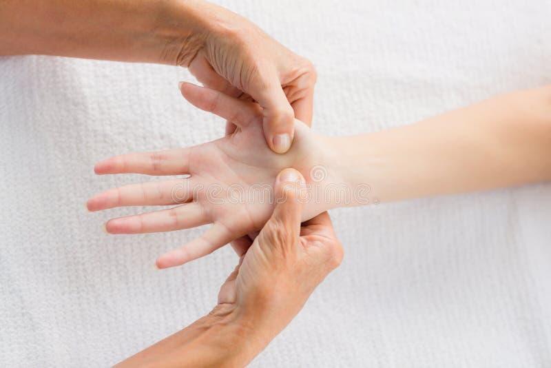 Imagem colhida do massagista que faz massagens a mão da mulher foto de stock royalty free