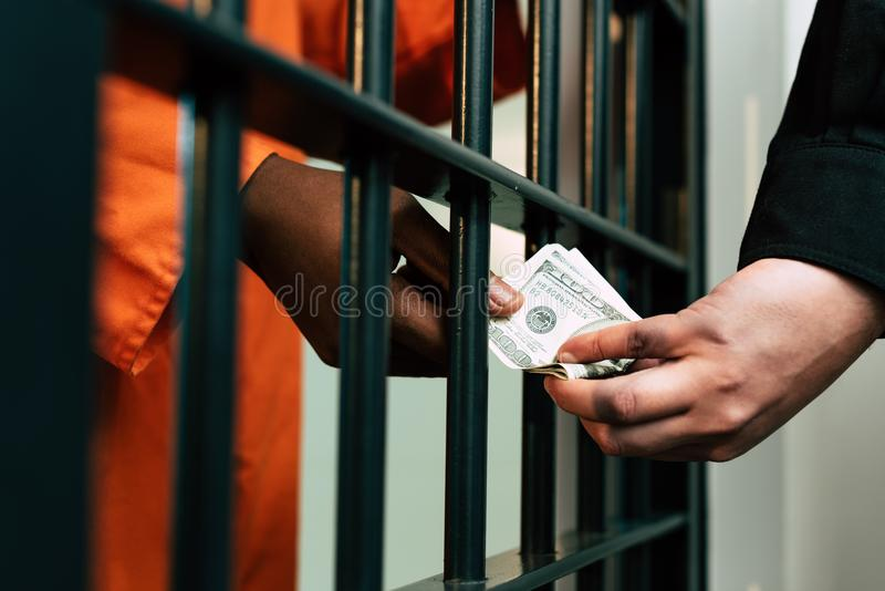 imagem colhida do prisioneiro afro-americano que dá o dinheiro à guarda de prisão foto de stock