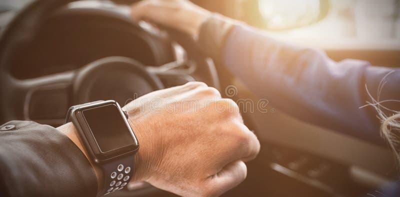 Imagem colhida do relógio de pulso vestindo da mulher no carro fotografia de stock