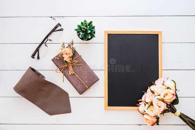 Imagem colocada lisa da caixa de presente, da gravata, dos vidros, da flor cor-de-rosa e do quadro do espaço vazio Vista superior fotos de stock