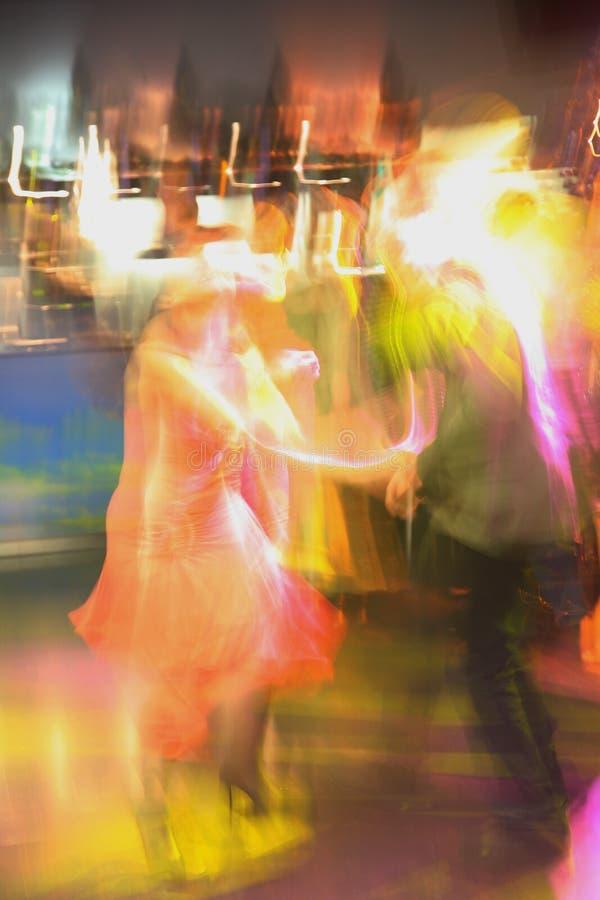 Imagem colorida ascendente próxima do borrão de movimento do sumário de povos felizes da dança em um clube de noite do disco fotografia de stock