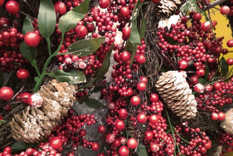 Imagem colorida do close up da decoração do Natal cones do pinho da árvore, maçãs, bagas vermelhas e varas de canela em ramos do  foto de stock