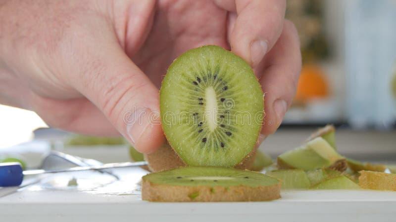 Imagem com mãos do homem na cozinha que apresenta uma fatia de Kiwi Fruit foto de stock royalty free