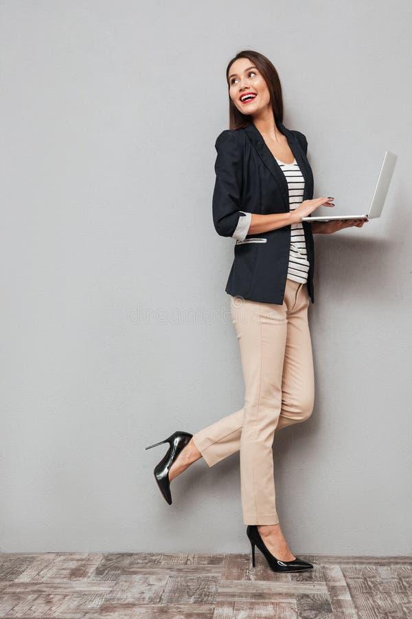 Imagem completa do comprimento da mulher de negócio feliz que guarda o laptop fotografia de stock
