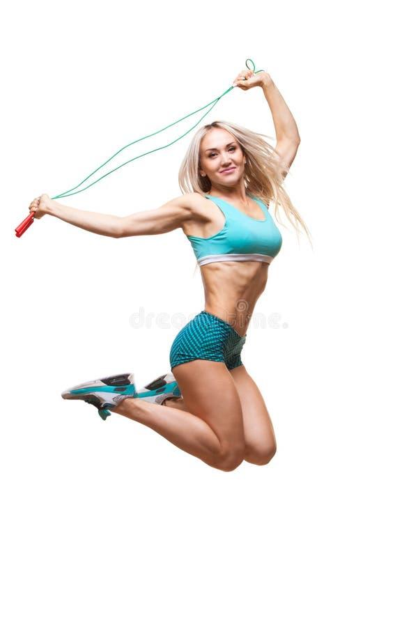 A imagem completa do comprimento de um jovem ostenta a mulher que salta na corda de salto sobre o fundo branco fotografia de stock royalty free