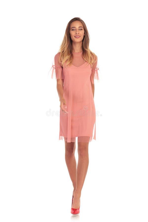 Imagem completa do corpo de uma mulher de sorriso que anda para a frente imagem de stock