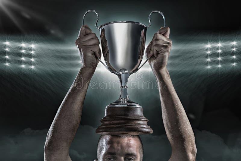 Imagem composta 3D do jogador bem sucedido do rugby que guarda o troféu imagem de stock