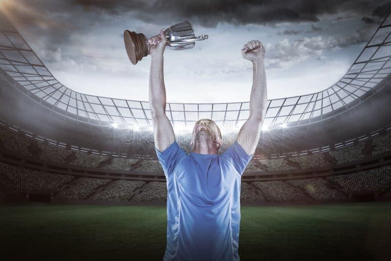 Imagem composta 3D do jogador feliz do rugby que guarda o troféu fotografia de stock
