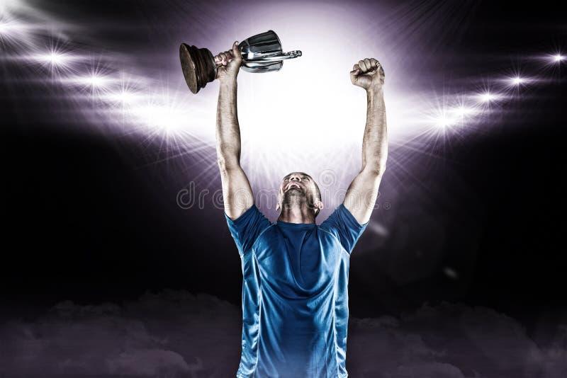 Imagem composta 3D do jogador feliz do rugby que guarda o troféu imagens de stock