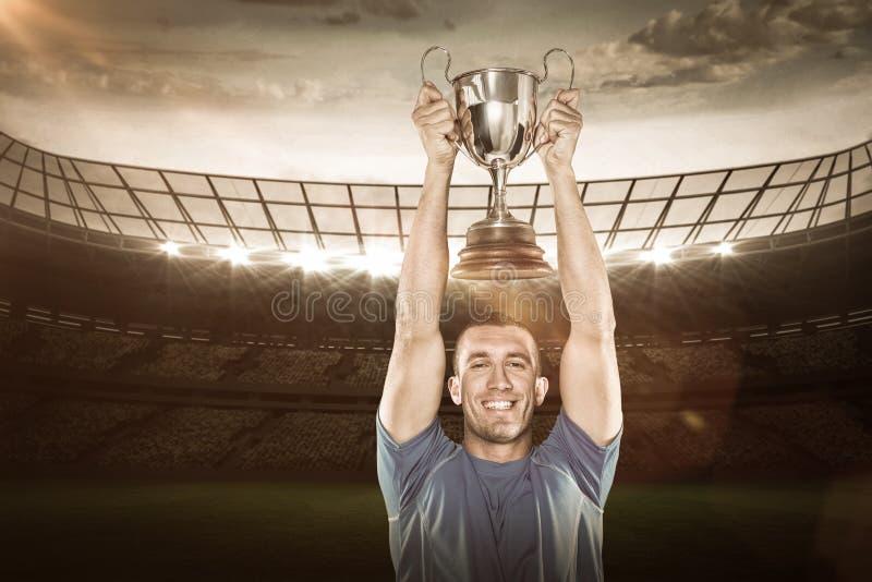 Imagem composta 3D do retrato do jogador de sorriso do rugby que guarda o troféu imagem de stock