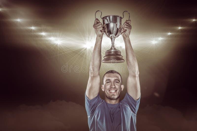 Imagem composta 3D do retrato do jogador de sorriso do rugby que guarda o troféu fotos de stock