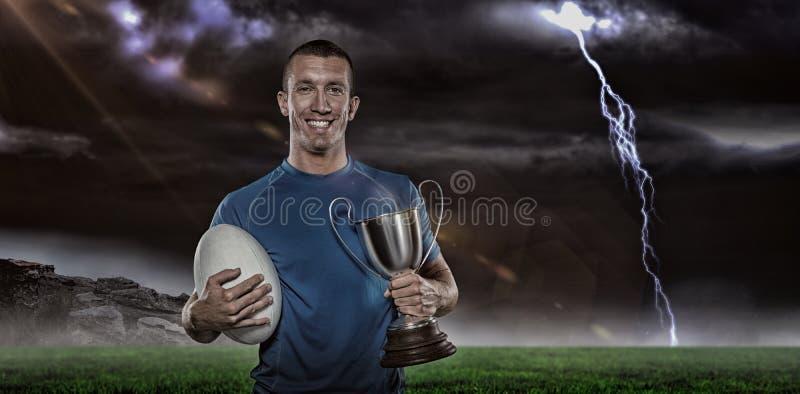Imagem composta 3D do retrato do jogador de sorriso do rugby que guarda o troféu e a bola imagem de stock