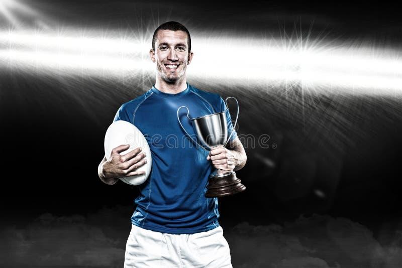 Imagem composta 3D do retrato do jogador de sorriso do rugby que guarda o troféu e a bola imagens de stock royalty free