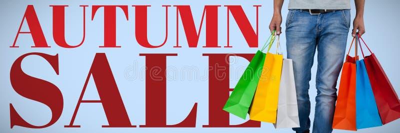 Imagem composta da baixa seção do homem que leva o saco de compras colorido contra o fundo branco imagem de stock