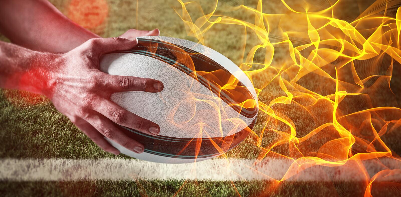 Imagem composta da bola de rugby da mão contra o fundo preto de incandescência da laranja abstrata fotografia de stock
