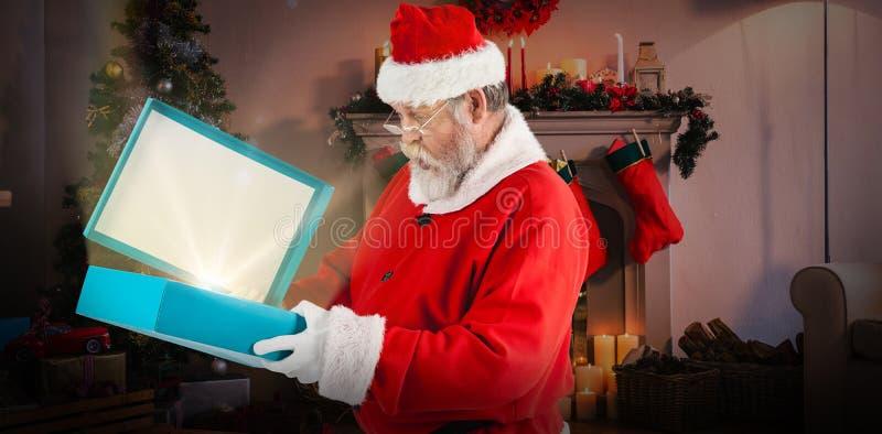 Imagem composta da caixa de presente da abertura de Papai Noel fotografia de stock