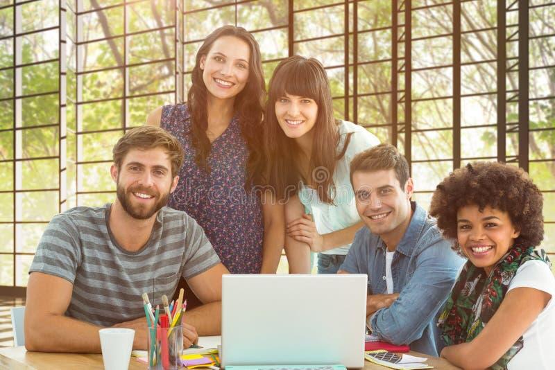 A imagem composta da equipe criativa feliz do negócio recolheu em torno de um portátil imagens de stock