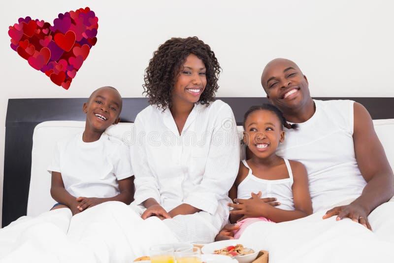 Imagem composta da família feliz que come o café da manhã na cama imagens de stock