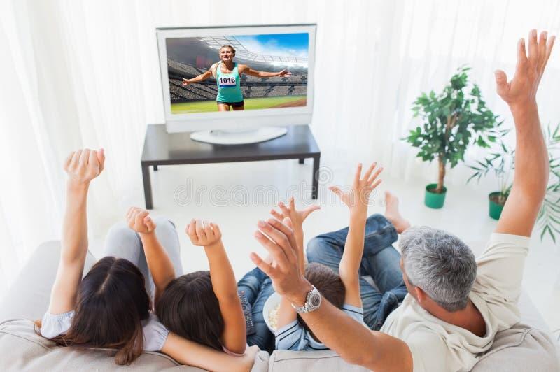 Imagem composta da família que aumenta seus braços na frente da televisão imagens de stock