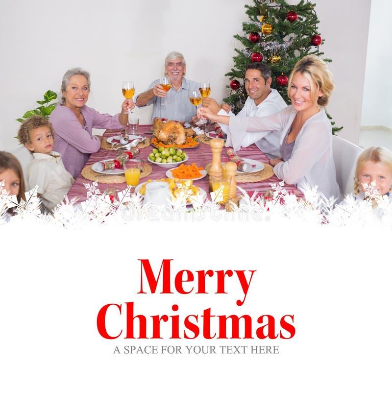 Imagem composta da família que aumenta seus vidros no Natal imagens de stock