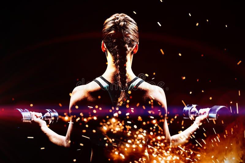 Imagem composta da ideia traseira de pesos de levantamento da mulher trançada do cabelo imagem de stock royalty free