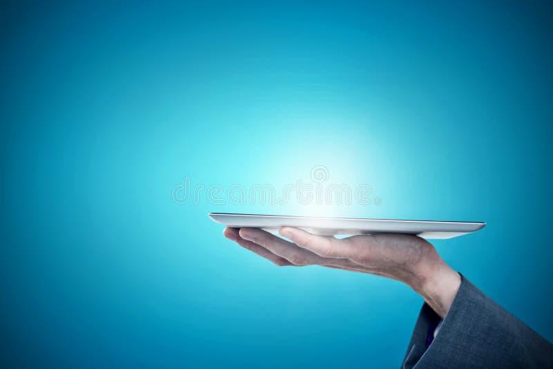 Imagem composta da mão colhida do homem de negócios que guarda a tabuleta digital imagens de stock royalty free