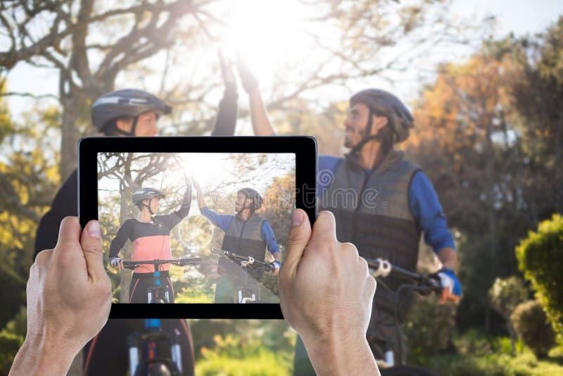 Imagem composta da mão colhida que guarda a tabuleta digital fotos de stock