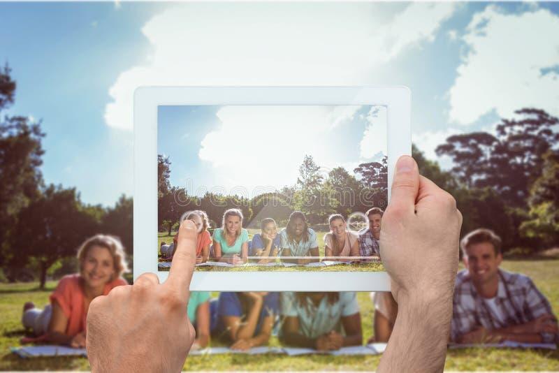 Imagem composta da mão que guarda o PC da tabuleta foto de stock