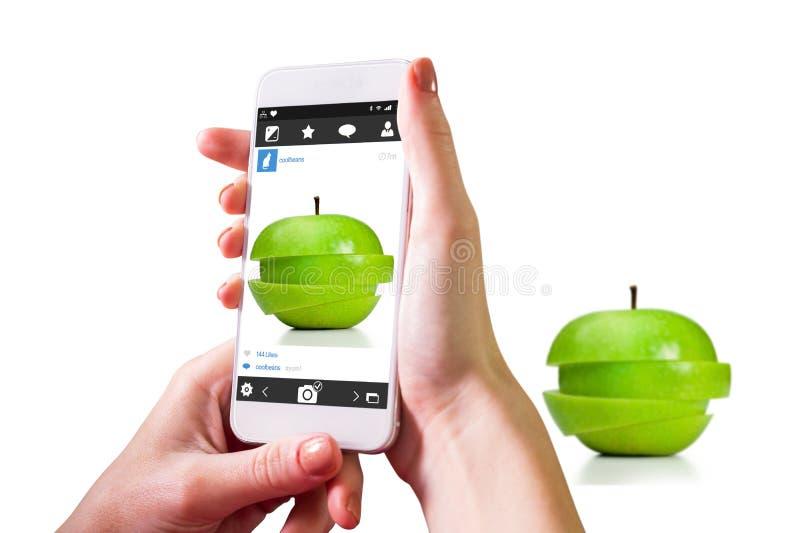 Imagem composta da mão que guarda o smartphone fotos de stock royalty free