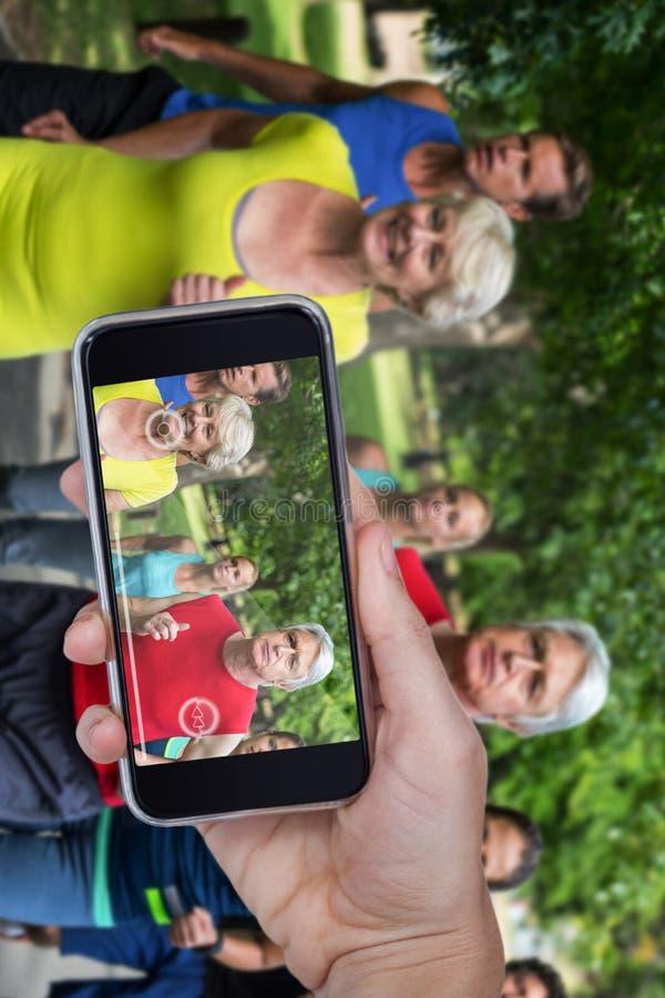 Imagem composta da mão que mantém o telefone celular contra o fundo branco foto de stock