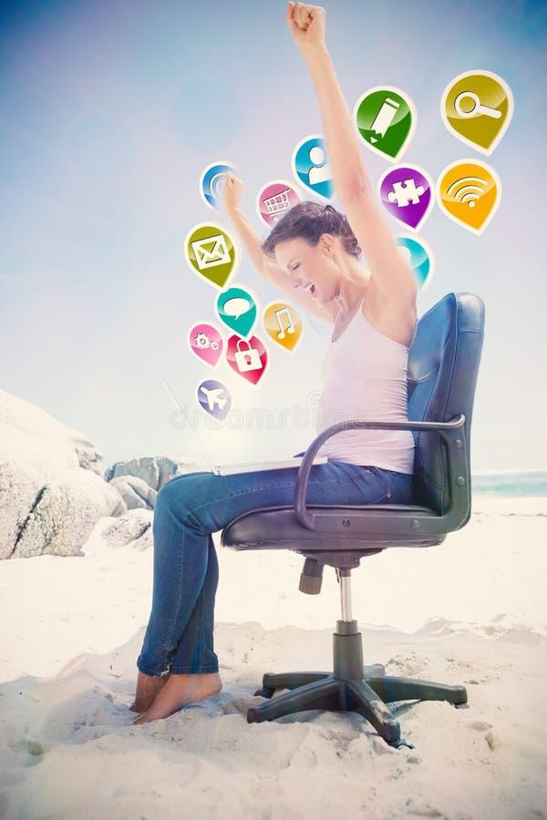 Imagem composta da morena cheering usando o portátil na praia que senta-se na cadeira de giro foto de stock