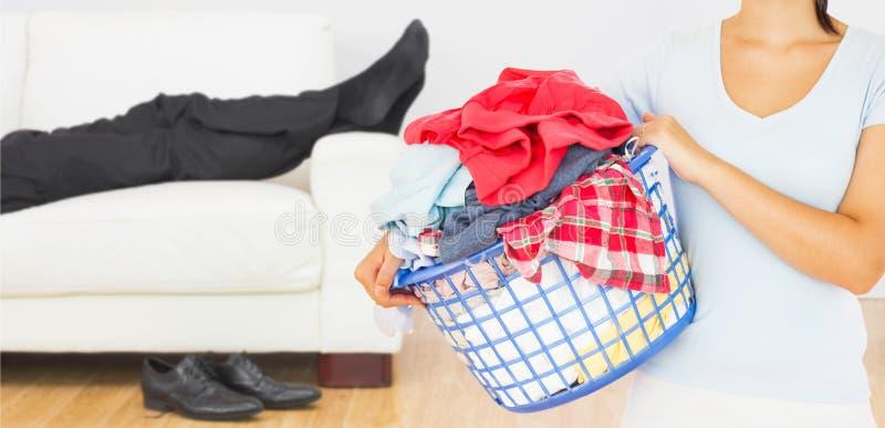 Imagem composta da morena que mantém uma cesta completa da lavanderia imagem de stock royalty free